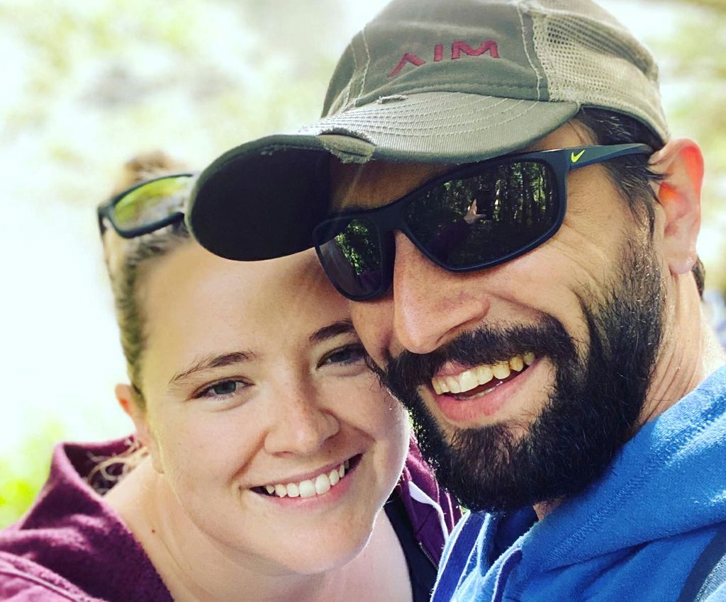 A close-in shot of a couple: Catherine Adams (left), a smiling woman with her hair pulled back; and her fiance (right), a smiling, bearded man in sunglasses and a ball cap