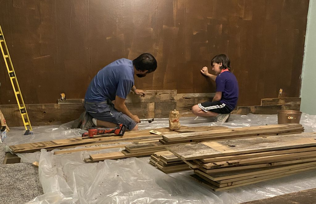 A man and boy work together on finishing a dark brown accent wall; stacked planks are in the foreground.
