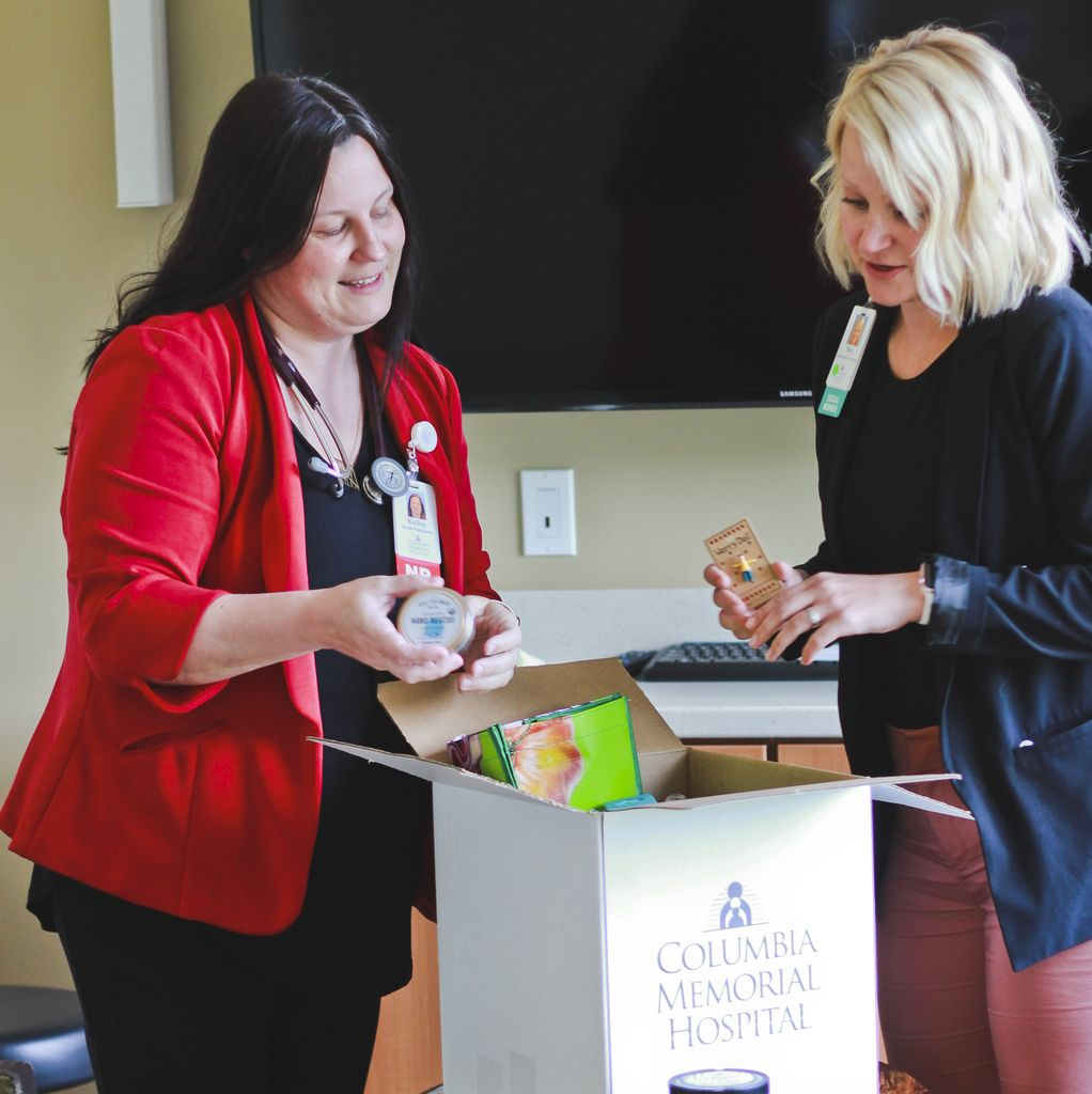 A dark-haired white woman (left) and light-haired white woman (right) put items into a cardboard box.