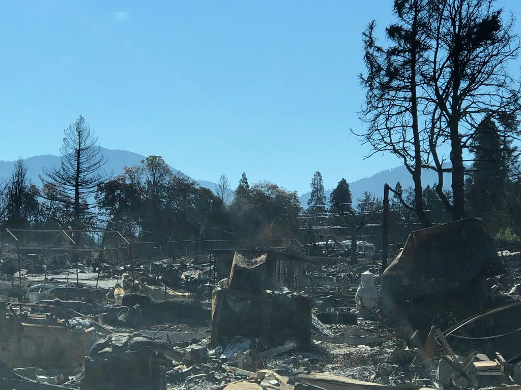 Structures, cars and trees blackened by wildfire, with blue sky and a foothill in the background.