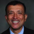 Headshot of Akram Khan, M.D., a smiling man with short, dark hair in a suit.