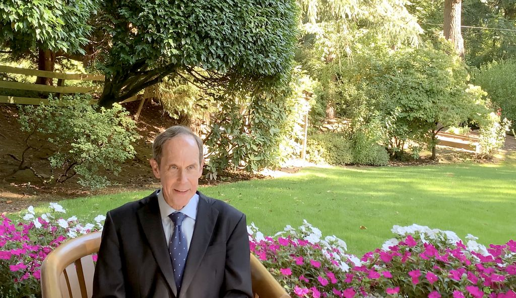 Brian Druker, M.D., a smiling white man in a suit, sits in a wooden chair with a garden in the background.
