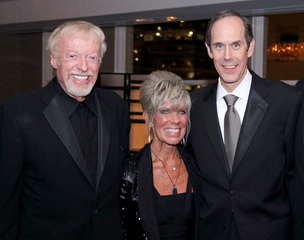 Phil and Penny Knight, a smiling caucasian couple in formalwear, pose with Dr. Brian Druker, a tall smiling white man in a suit.
