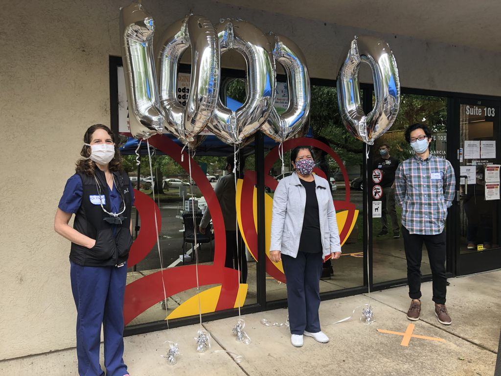 "A white masked woman (left) stands with a masked Hispanic female patient (center) and a masked Asian male volunteer (right) stand in front of a clinic's glass windows with 5 numeral balloons reading ""10,000"" (1, 0, 0, 0, 0 from left to right)."