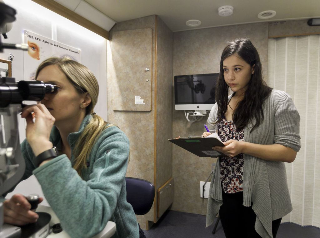 A seated, blond, white woman (left) looks into an opthamalogical assessment instrument's eye pieces while a dark-haired woman (right) stands behind her with a clipboard in a mobile medical office.