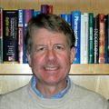 Headshot of Martin Kelly, Ph.D., a smiling white man in a sweater, posing in front of a bookshelf.