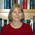 Headshot of Oline Ronnekleiv, Ph.D., a smiling white woman in a red sweater, posing in front of a bookshelf.