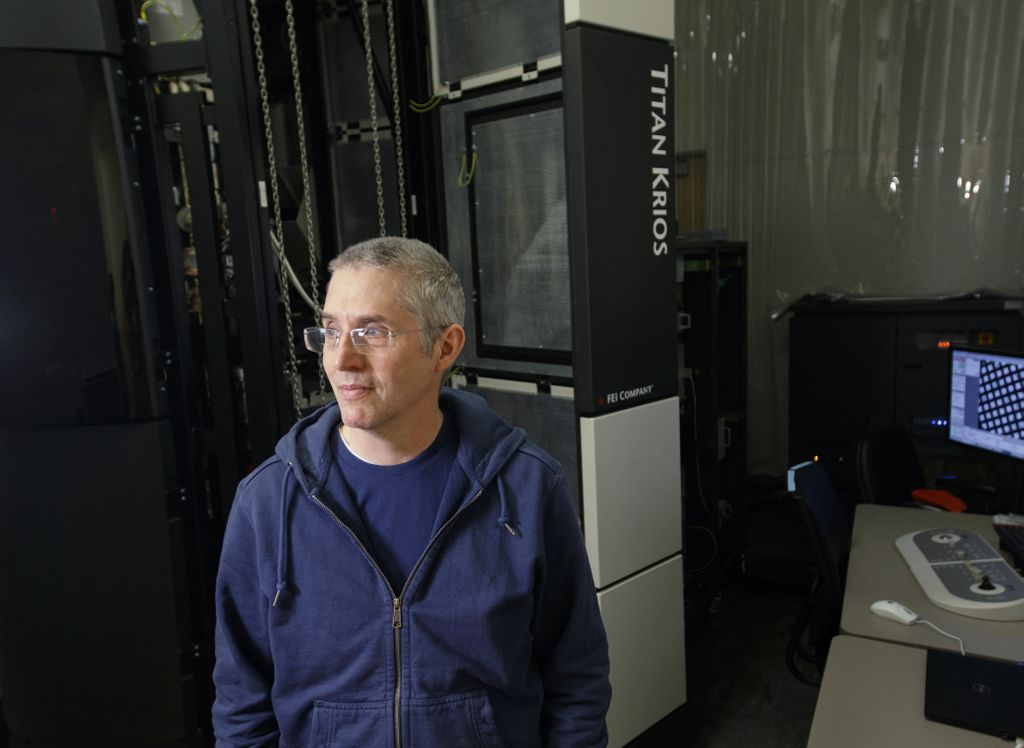 Eric Gouaux, Ph.D., a white man with short grey hair and glasses, stands in front of cryo-EM lab equipment.