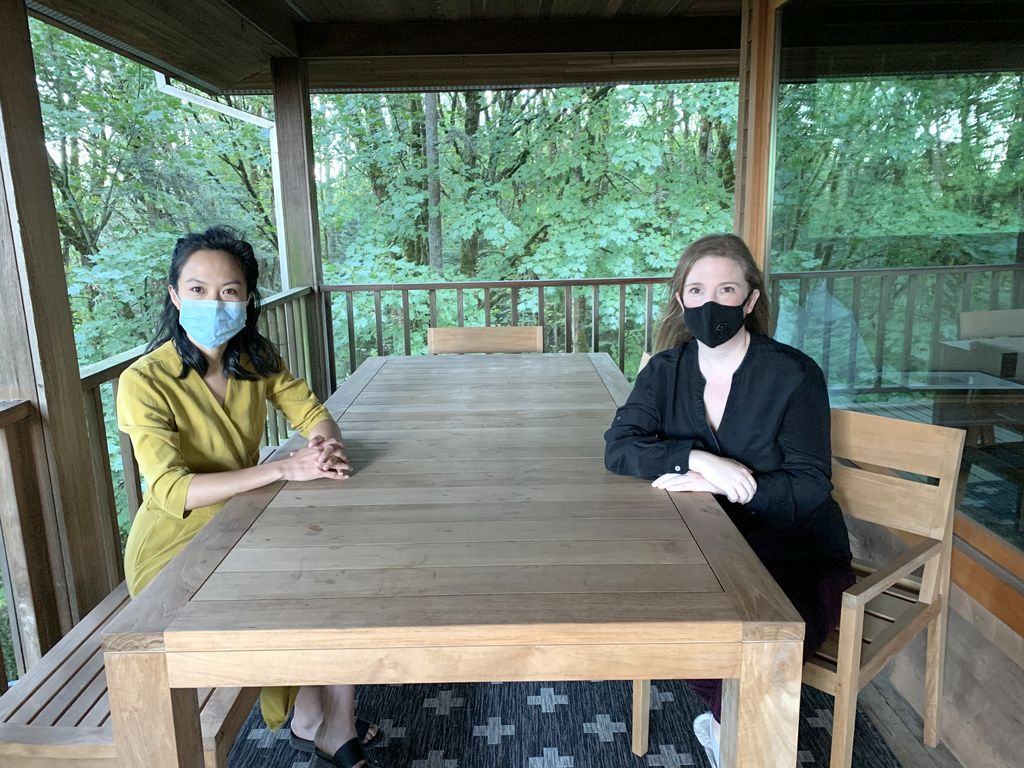 Founders of Urologists for equity, masked females Dr. Geolani Dy (left) and Dr. Casey Seideman (right), sit across from each other at a wooden table with trees visible through the large exterior windows.