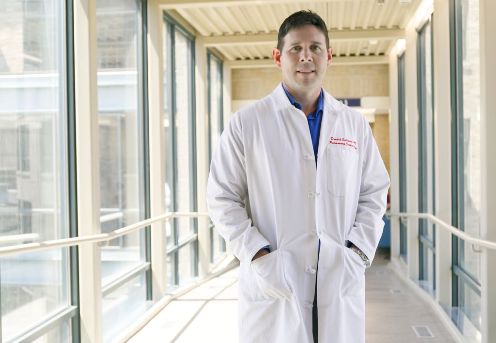 Donald Sullivan, a white man in a white lab coat, stands in a sunny hospital walkway with his hands in his pockets.