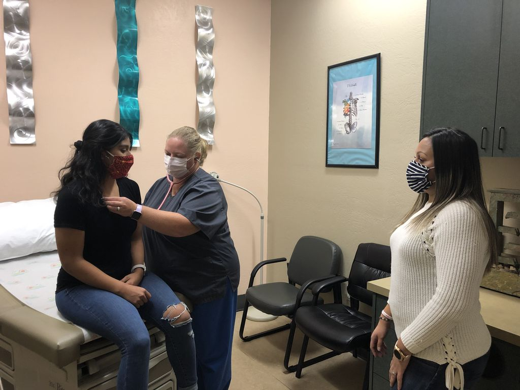 A dark-haired, masked woman sits on an exam table in a medical office; a second masked woman uses a stethoscope on the first woman's chest; a third masked woman stands in the room to interpret to and from Spanish.