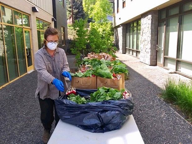 A masked white woman in a grey cardigan stands over an outdoor table of vegetables, packing them for delivery.
