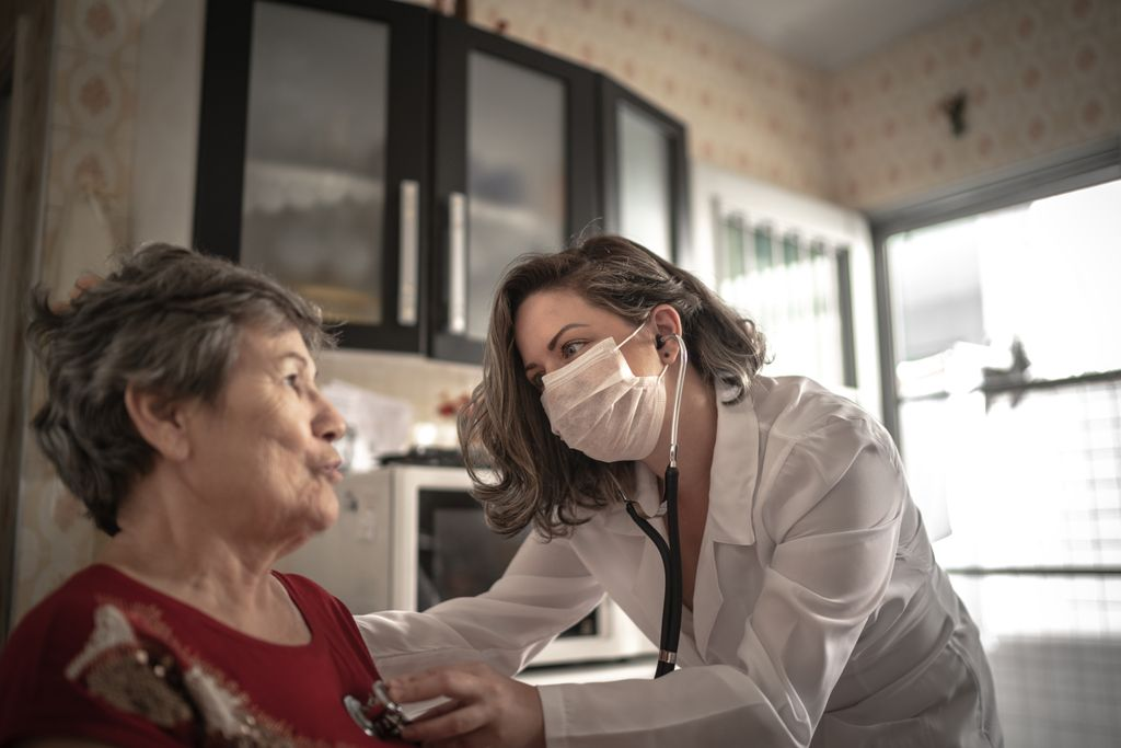 A masked female health care provider in a white lab coat checks a senior woman with a stethoscope during a home visit.