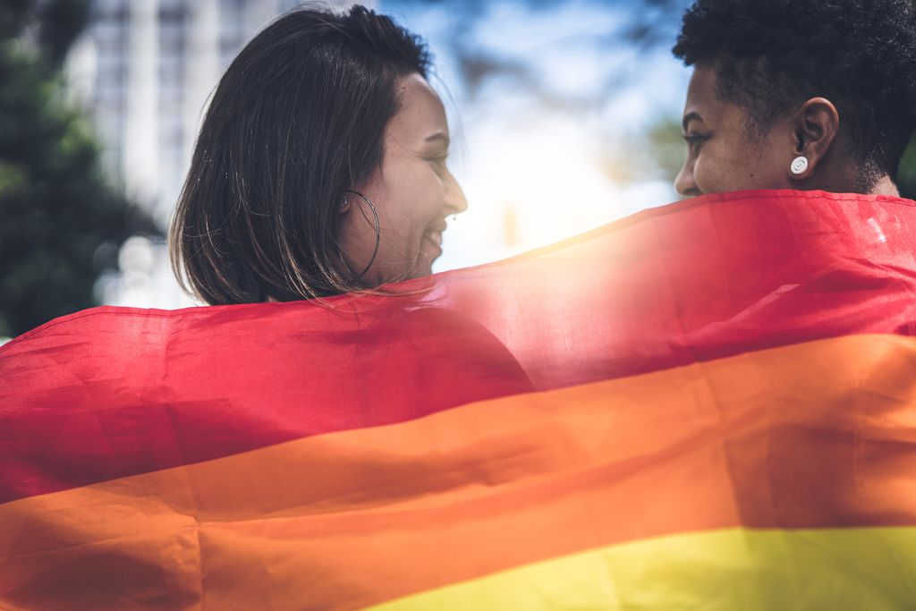 Two women's smiling faces visible above a rainbow flag,