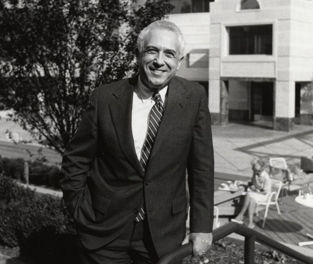 Black and white photo of Leonard Laster, M.D., a smiling white man in a suit, standing at The Vollum Institute at OHSU in Portland, Oregon.