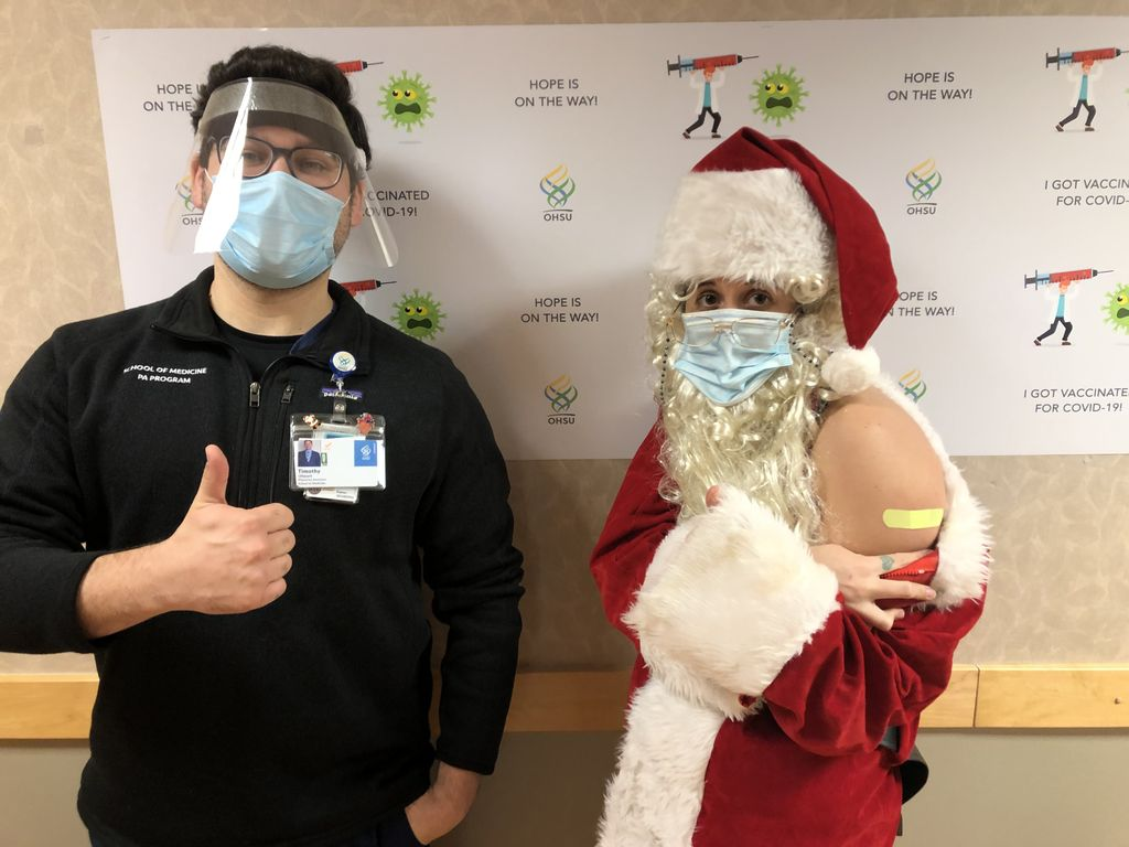 A male Physician's Assistant student (left) wearing a surgical mask and face shield stands giving a thumbs up. A woman in a Santa suit, white costume beard and sugrical mask shows the Band-aid on her shoulder where she received her COVID-19 vaccination shot