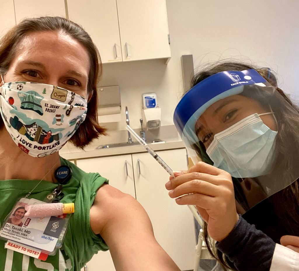 A lean caucasian woman in a face mask offers her shoulder to a masked and shielded Asian female who is holding a syringe of COVID-19 vaccine