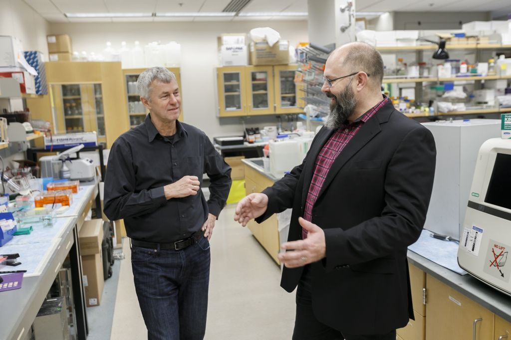 Two caucasian males stand talking in a medical lab; the clean-shaven man on the left has white hair and wears a black button-down shirt; the bearded, bald man on the right wears a plaid shirt and black blazer; medical and lab equipment are around them and in the background