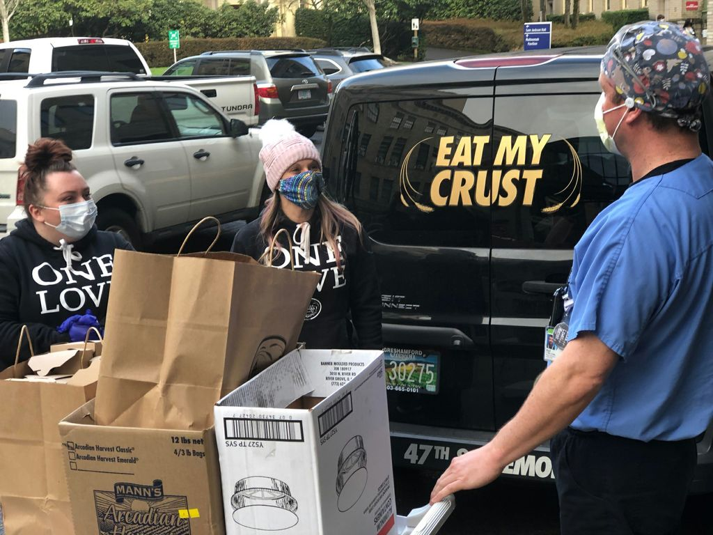 Two masked female adults bring bags of pasta meals to a masked OHSU employee in scrubs and a mask, where he is loading them onto a white wheeled cart