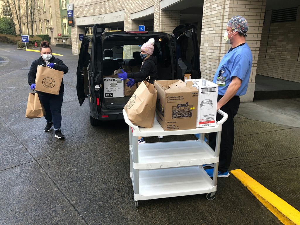 Two masked females bring brown bags of pasta meals to a masked OHSU employee in scrubs, who is loading them onto a white wheeled cart