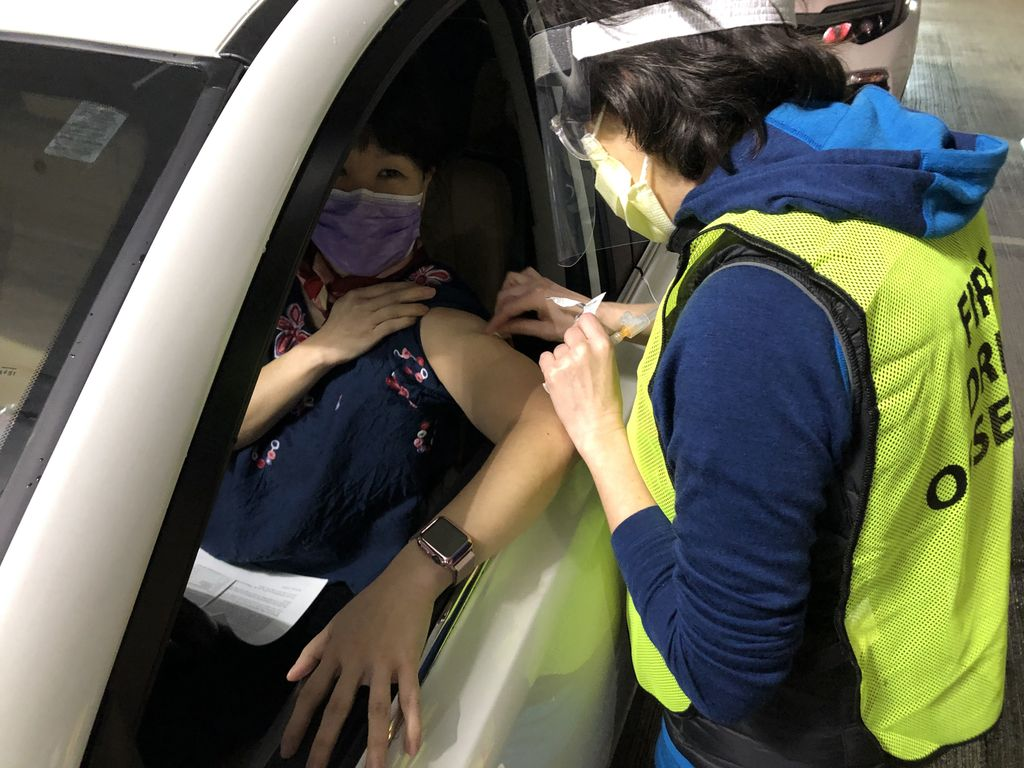 masked health care worker gives injection into the shoulder of a woman in the driver seat of a car