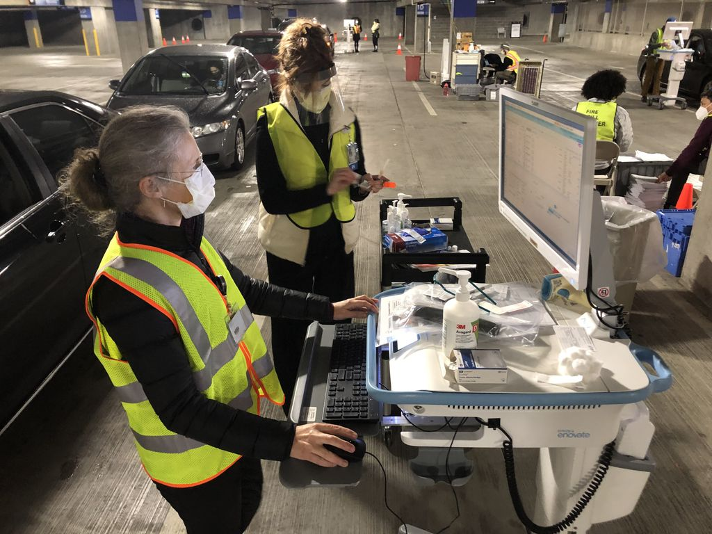 An OHSU doctor and an OHSU nurse in masks and safety vests prepare to vaccinate a caregiver at a drive-up vaccine clinic in the Oregon Convention Center parking garage. Doctor checking the patient's record on a portable computer; nurse is preparing the vaccine.