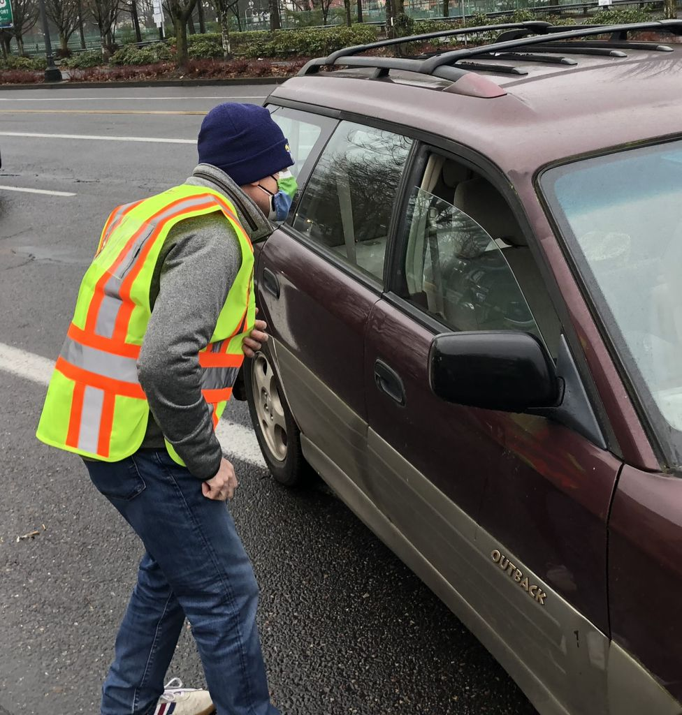 OHSU leader in yellow safety vest, mask and stocking cap directs traffic outside the Oregon Convention Center parking garage-turned vaccine clinic.