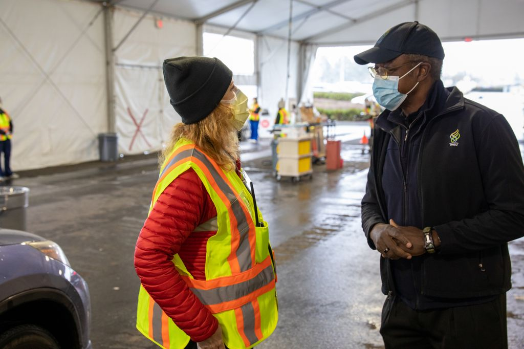 OHSU President Danny Jacobs talks with Debbie Lamberger, director of ambulatory operations, at the outdoor/tented Hillsboro Stadium drive-through vaccination clinic Jan. 10. Both are wearing masks and safety vests.