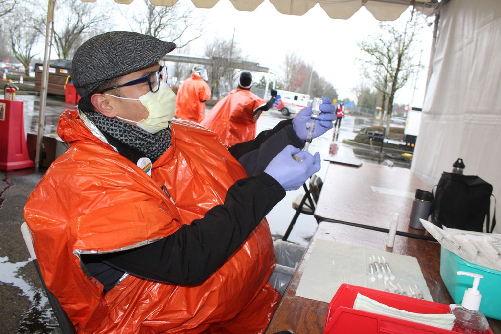 Man in orange poncho handles a syringe and vial.