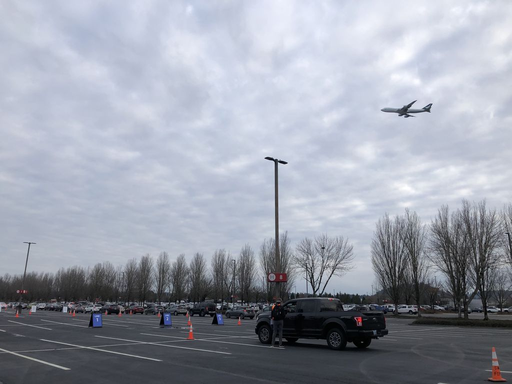 Plane visible overhead as vehicles que in airport parking lot.