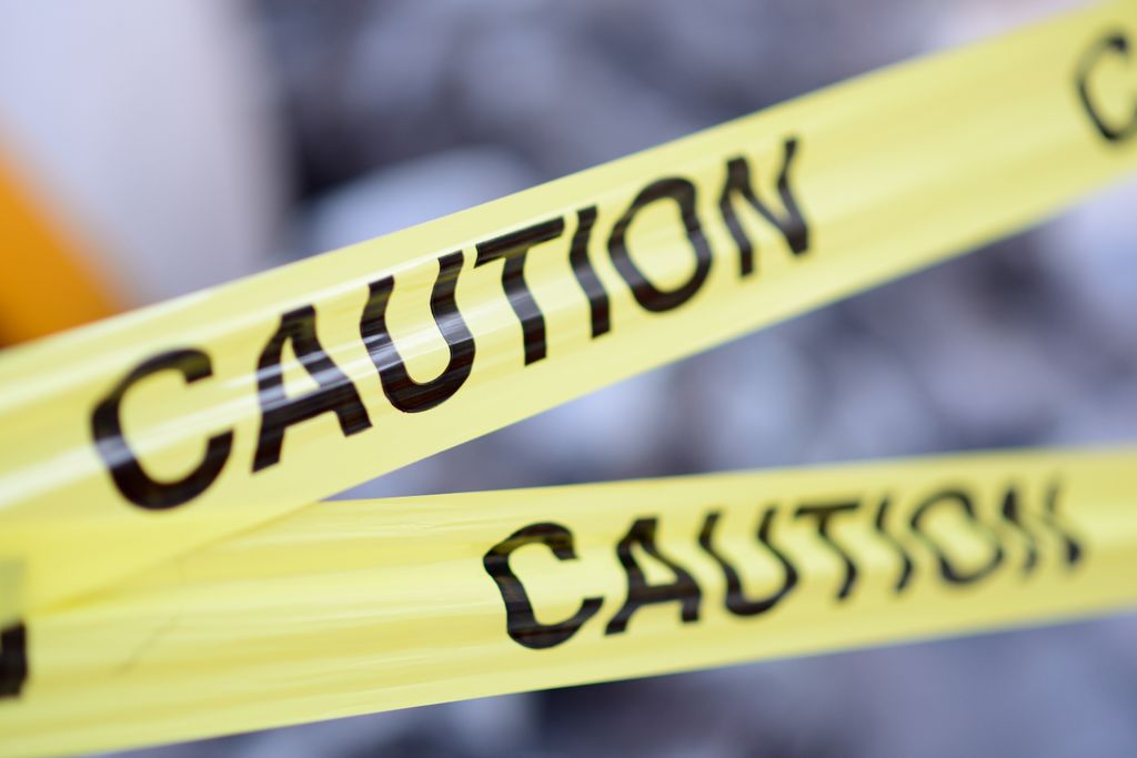 two pieces of yellow 'caution' tape are in focus in the foreground; background is blurred.
