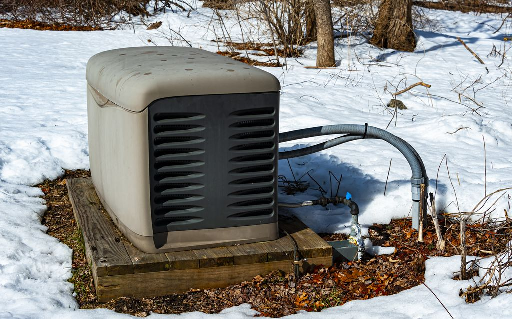 Residential generator outdoors in the snow, atop a wooden platform