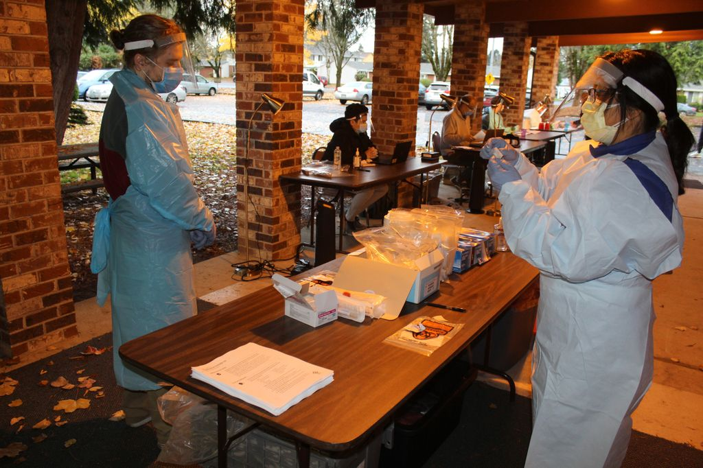 Two people clad in visors, masks and blue surgical gowns prepare testing materials at a table.
