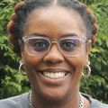 Close-in headshot of Nichole Watson, a Black woman smiling wearing glasses