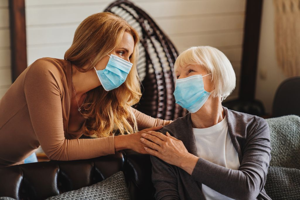 a senior woman and her adult daughter wear protective face masks and clasp hands