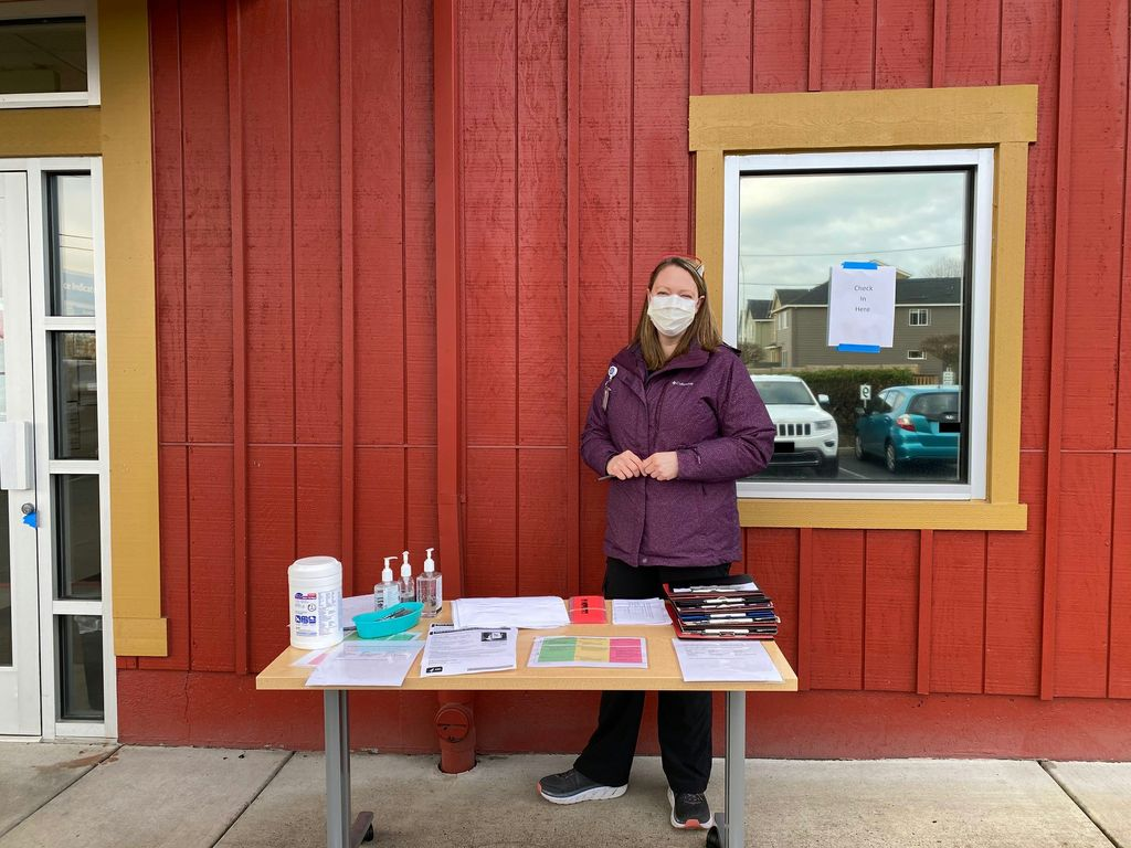An adult woman in a protective mask stands at an information table in front of a red building; a sign on the window behind her reads 'check in here'