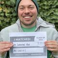 "Douglas Rice, a caucasian male wearing a beanie hat, smiles while holding a sign that says ""I matched!"""