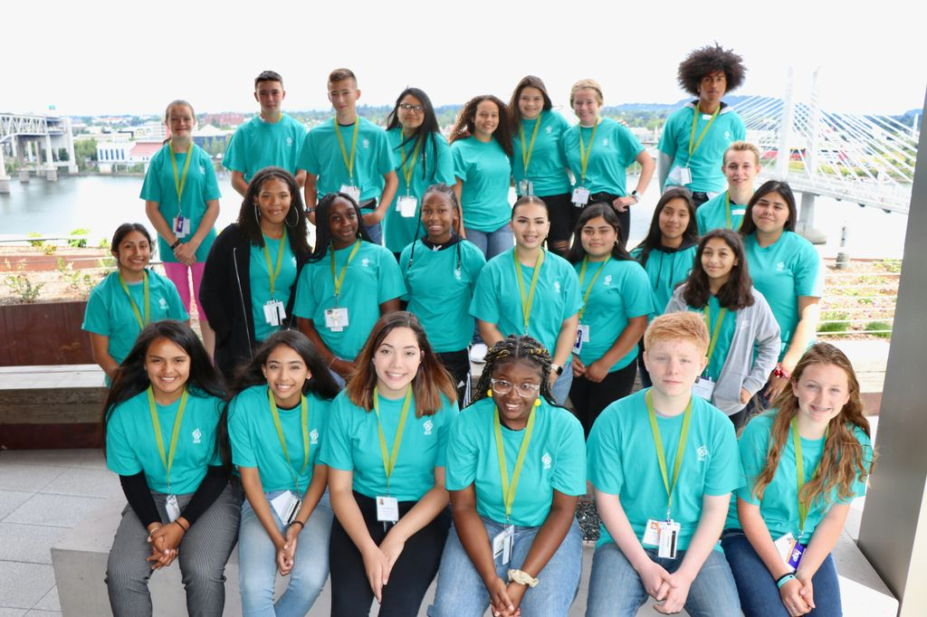Knight Scholars group photo: three rows of students in matching teal t-shirts look at the camera