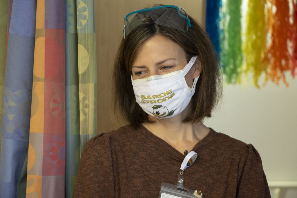 """Woman with safety glasses propped atop her head smiles behind a face mask that reads """"Barde Strong."""""""