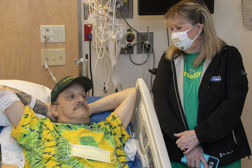 Woman wearing a face mask looks down and smiles at relaxed man laying in hospital bed.