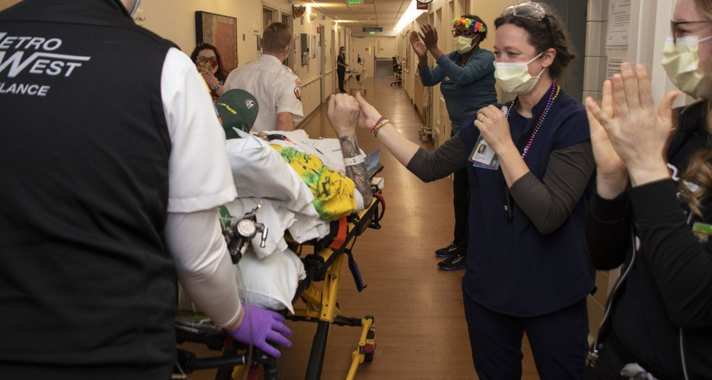 A health care worker wearing scrubs and Mardis Gras beads grasps the arm of a man laying in a stretcher who is being wheeled past a hallway lined with applauding staff.