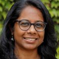 Headshot of Swetha Murthy Ph.D., a dark-skinned adult with bushes behind her.