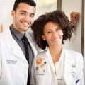 Shane Hervey and Kelley Butler, two Black adults, pose together wearing white doctor coats