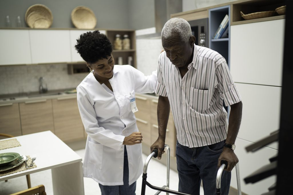 a healthcare worker assists a senior Black man with a walker