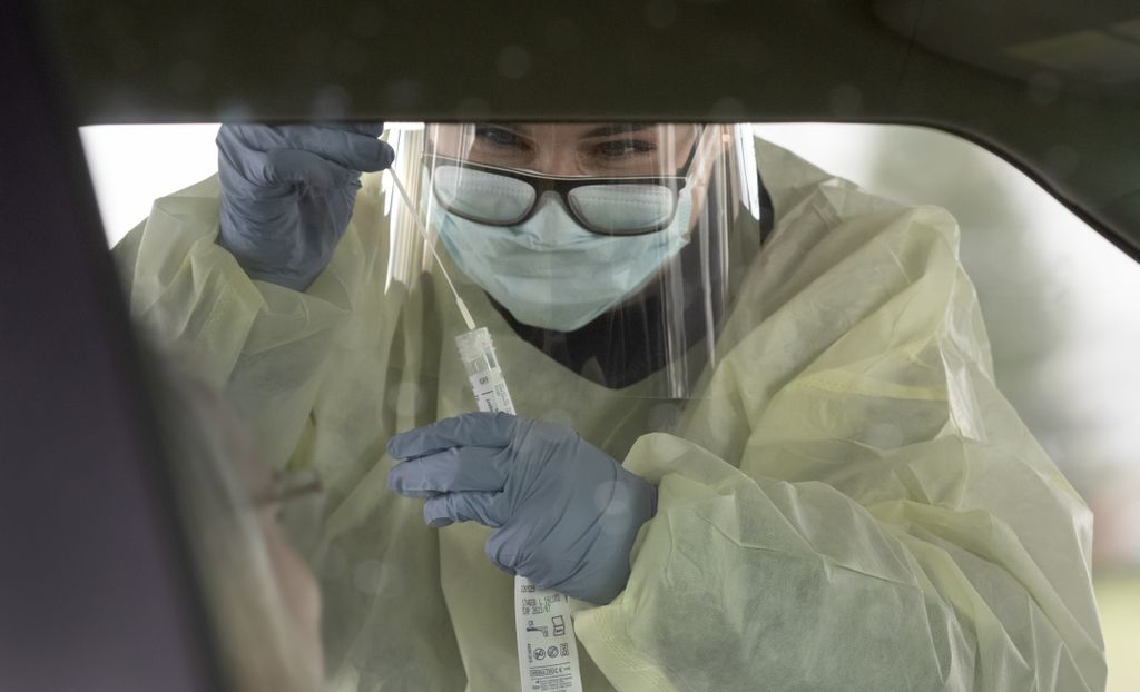 A woman leans into the car window as she peers through glasses and a clear face visor to insert a specimen swab into a plastic sleeve.