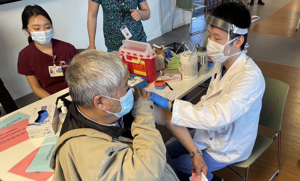 Male physician assistant student dabs an older man's upper arm where he vaccinated him at a community-run clinic. Both are wearing medical masks.
