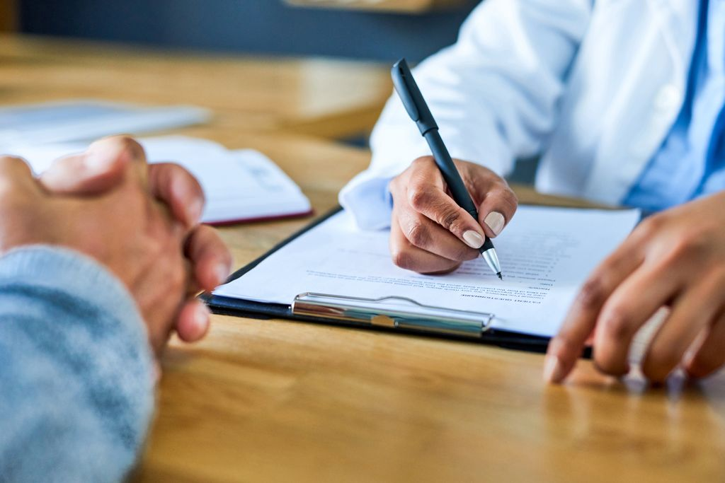 Closeup shot of a doctor's hands writing notes on a pad during a consultation with a patient