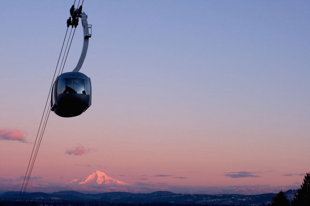 Portland Aerial Tram in silhouette at sunrise, with Mt. Hood visible against the pink and purple sky
