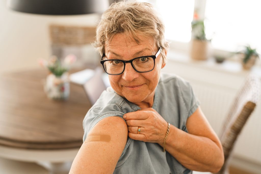 A senior woman that has received her COVID-19 vaccine. She is pulling up her sleeve to show the bandage.