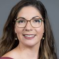 Close-in headshot of Ximena A. Levander M.D. M.C.R., a smiling woman with long brown hair, wearing glasses